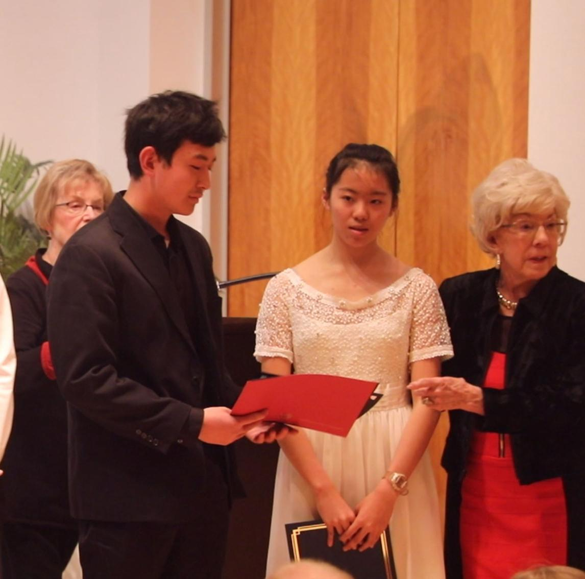 Wesley Dong, 2019 Second-Place Winner in Piano, accepts his certificate and prize money.  Jane Wei, First-Place Winner, and Jackie McGehee are to his right
